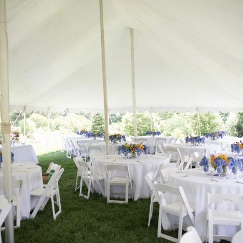 Wedding Reception with White Tablecloths and Colorful Centerpieces Outside Under a Large White Tent